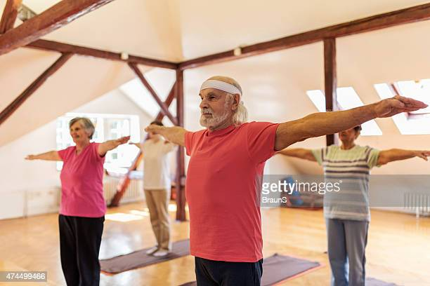 Group of seniors exercising with their arms outstretched.