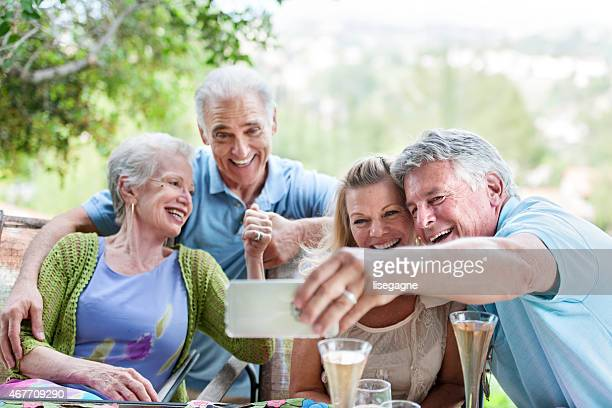 Group of seniors having an outdoors party, taking selfie