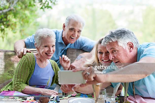 Gruppo di anziani avendo una festa all'aperto, e fanno selfie