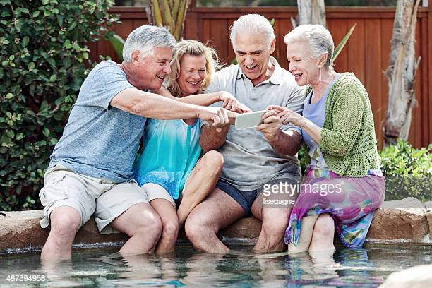 Group of seniors looking at pictures in the jacuzzi