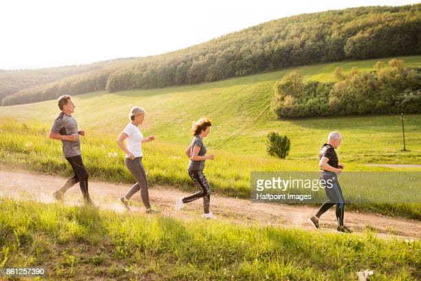 Group of seniors running in nature on dirt road.