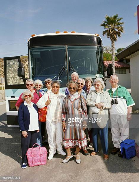 Group of seniors standing in front of tour bus