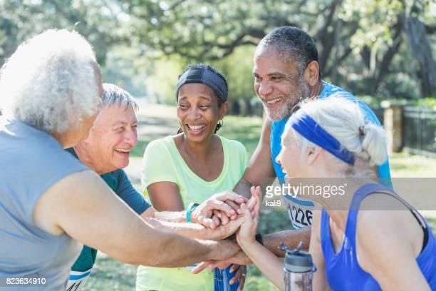 Grupo de personas mayores hablando en final de carrera, las manos juntas