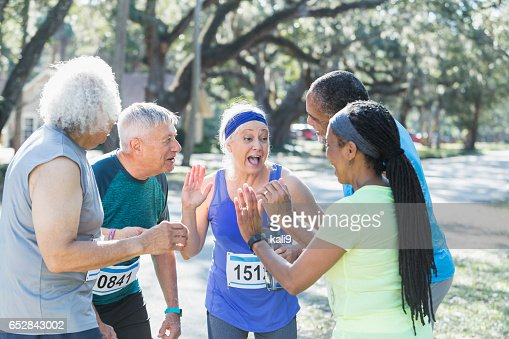 Group of seniors talking at end of race, high fives : Foto stock