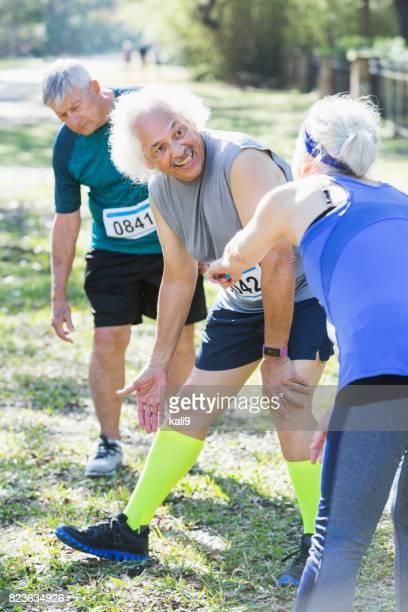 Grupo de personas mayores lleva contados baberos para la carrera, hablando