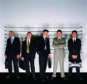 Group of Serious Businessmen Standing Holding Briefcases in a Police Line-up and a Man With His Arms Crossed