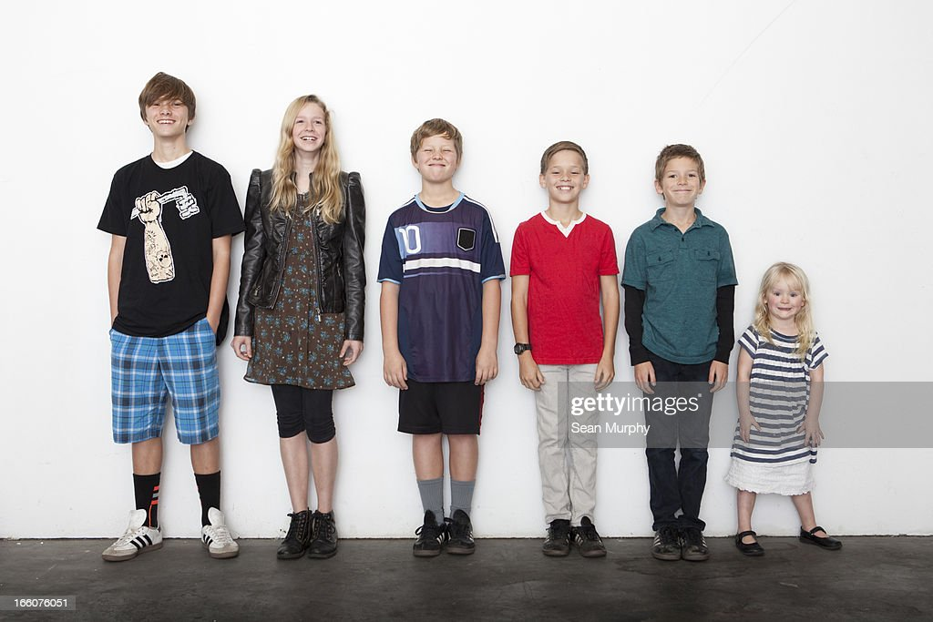Group of sibling in line against white wall