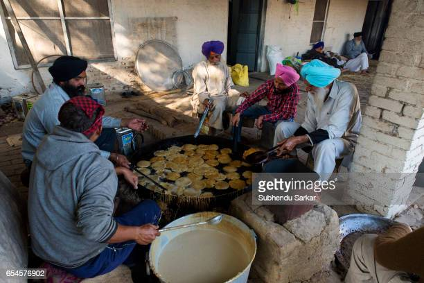A group of Sikh men cook at a langar to feed the devotees during Hola Mohalla festival Hola Mohalla is a threeday festival started by the tenth Sikh...