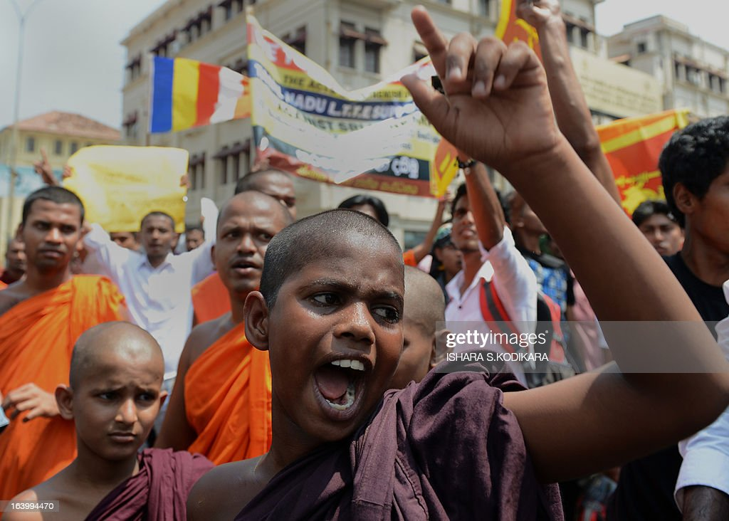 A group of Sinhala Rawaya Buddhist monks carry placards as they march towards the Indian High Commission in protest against attacks against Sri Lankans visiting the south Indian state of Tamil Nadu, in Colombo on March 19, 2013. The monks sought Indian central government's intervention to stop assaults against Sri Lankan pilgrims as ties between the two nations remained tense over alleged rights violations of minority Tamils by Sri Lanka's Sinhalese-dominated government. Tamils in south India share close cultural and religious links with their counterparts in Sri Lanka. AFP PHOTO/ Ishara S