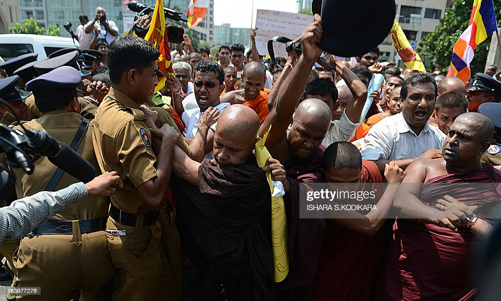 A group of Sinhala Rawaya Buddhist monks push through police barricades to march to the Indian High Commission in protest against attacks against Sri Lankans visiting the south Indian state of Tamil Nadu, in Colombo on March 19, 2013. The monks sought Indian central government's intervention to stop assaults against Sri Lankan pilgrims as ties between the two nations remained tense over alleged rights violations of minority Tamils by Sri Lanka's Sinhalese-dominated government. Tamils in south India share close cultural and religious links with their counterparts in Sri Lanka. AFP PHOTO/ Ishara S.KODIKARA
