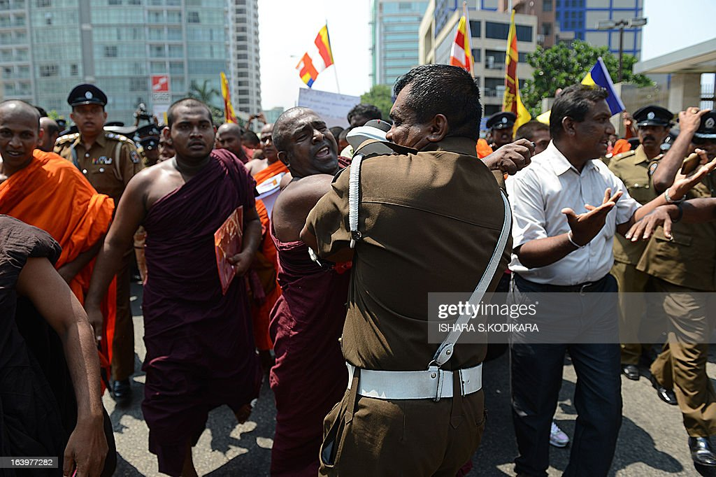 A group of Sinhala Rawaya Buddhist monks push through police barricades to march to the Indian High Commission in protest against attacks against Sri Lankans visiting the south Indian state of Tamil Nadu, in Colombo on March 19, 2013. The monks sought Indian central government's intervention to stop assaults against Sri Lankan pilgrims as ties between the two nations remained tense over alleged rights violations of minority Tamils by Sri Lanka's Sinhalese-dominated government. Tamils in south India share close cultural and religious links with their counterparts in Sri Lanka. AFP PHOTO/ Ishara S