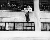 A group of sitdown strikers peer from the windows of the Chevrolet Plant in Flint Michigan in December of 1936 after the start of a 43 day strike of...