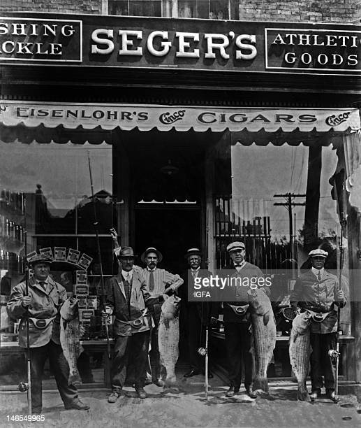 A group of six men stand in front of Seger's store Four of the men members of the Asbury Park Fishing Club hold fishing rods and striped bass caught...