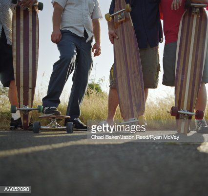 Group of skaters standing with longboards, low section : Stock Photo