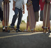 Group of skaters standing with longboards, low section