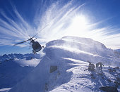 Group of  skiers on mountain top with helicopter