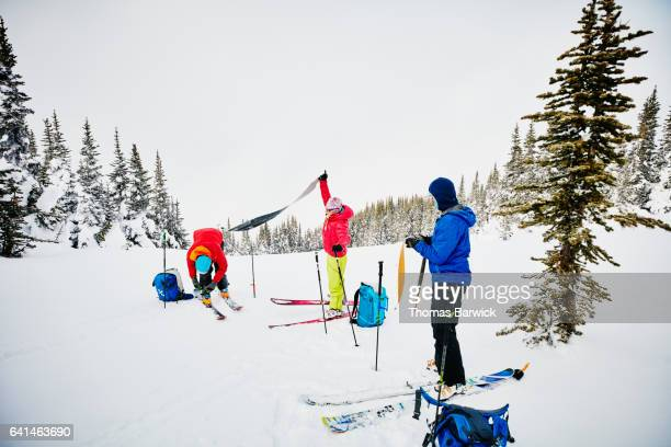 Group of skiers removing skins from skis before descending on backcountry ski tour