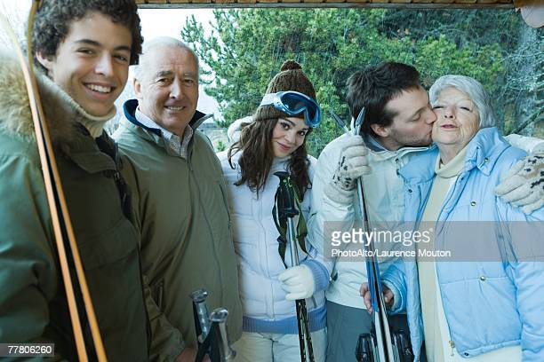 Group of skiers, young man kissing senior woman on check, portrait