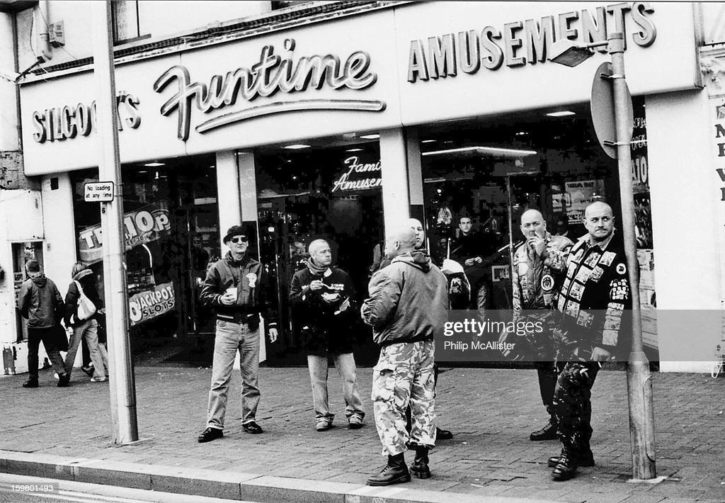 CONTENT] A group of skinhead scooterists gather outside an amusement arcade.Some are smoking and some are eating chips.They look nonchalant as one leans casually on a lamp post. The image is captured on a film camera and is very gritty and contrasty.It is black and white.