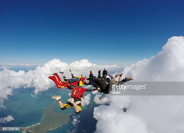 Group of skydivers between clouds and sea