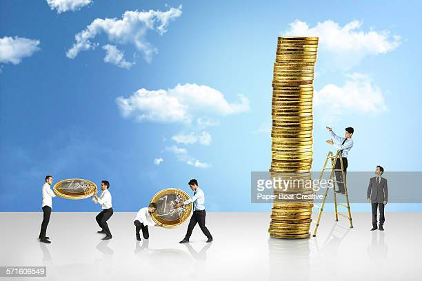 Group of small businessmen building stack of coins