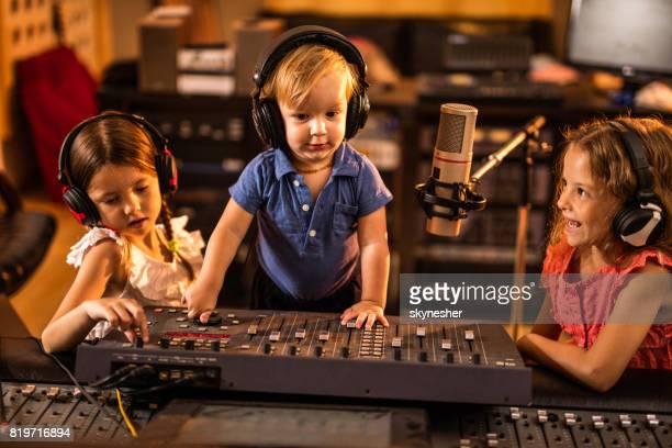 Groupe de petits enfants qui travaillent ensemble dans une station de radio.