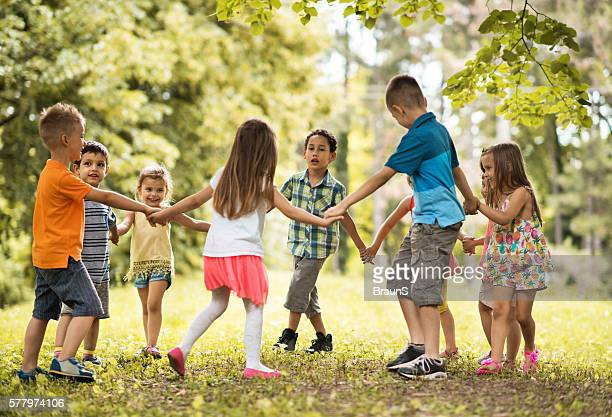 Group of small kids playing ring-around-the-rosy in the park.