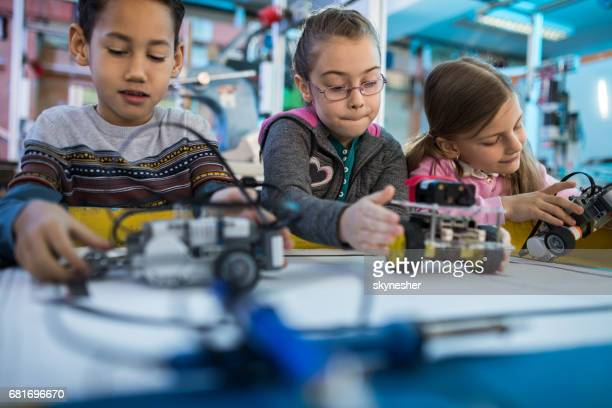 Group of small kids working on robots on a robotics class.