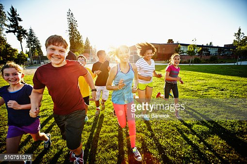 Group of smiling boys and girls running on field : Stock Photo