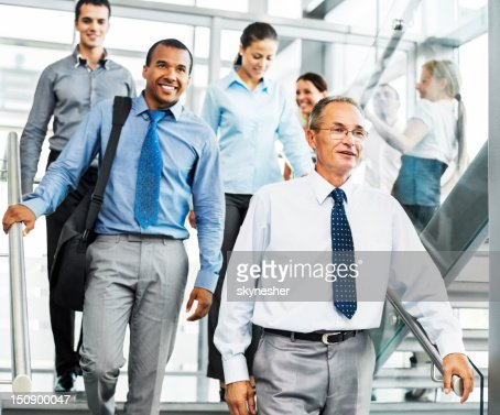 Group of smiling businesspeople on the staircase