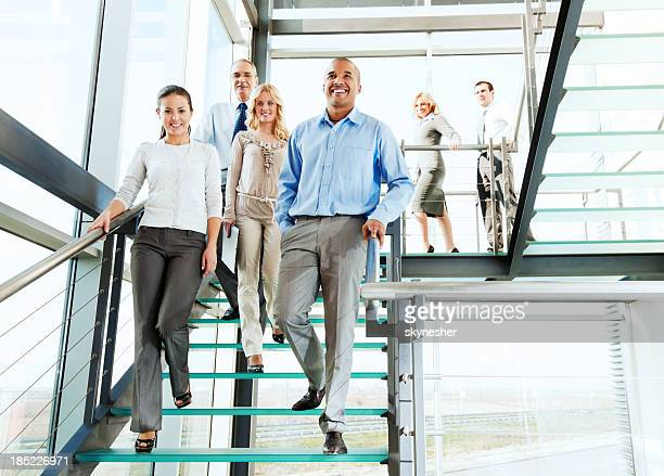Group of smiling businesspeople on the staircase.