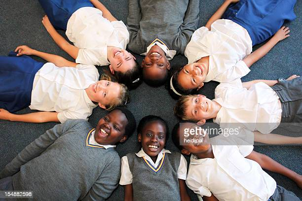 Group of smiling children lying in a circle