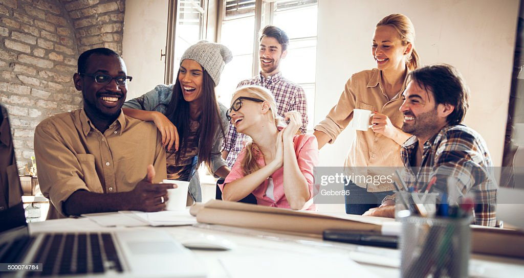 Group of smiling designers relaxing : Stock Photo
