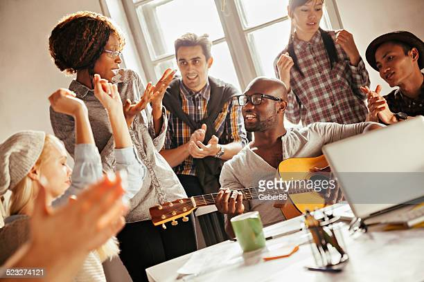 Group of smiling designers relaxing with guitar