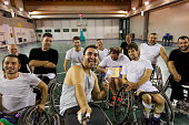 group of smiling disabled basketball players on a wheelchair take a selfie in a basketball court