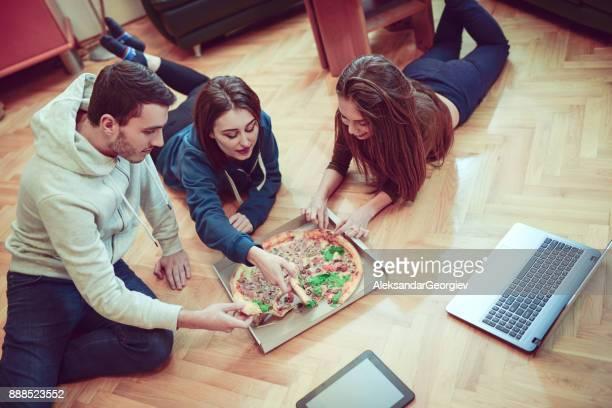 Grupp av leende vänner dela en Pizza ligger på ett golv hemma