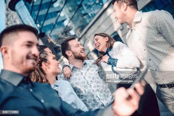 Gruppe von lächelnden Freunde freigeben von Medien mit Smartphone in Stadt
