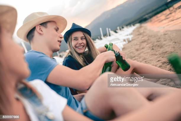 Group of Smiling Friends Sitting at Beach and Drinking Beer