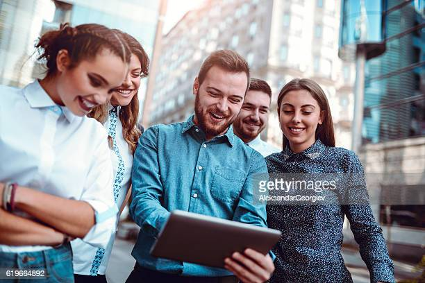 Group of Smiling Friends Surfing the Net in the City