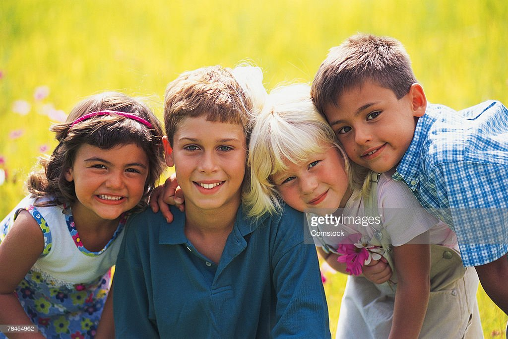 Group of smiling kids posing in field : Stock Photo