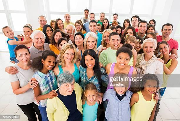 Gruppe von lächelnden Menschen, umarmen und Blick in die Kamera.