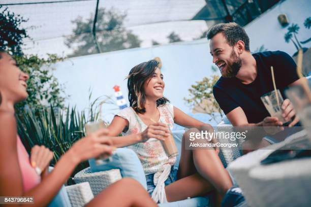Group of Smiling People Socialising and Drinking Coffee in Backyard