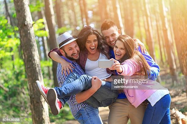 Groupe de souriant jeunes s'amusant dans la forêt