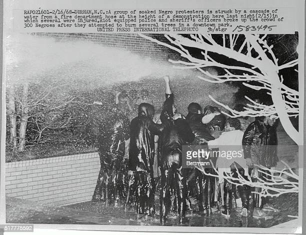 A group of soaked Negro protesters is struck by a cascade of water from a fire department hose at the height of a demonstration last night in which...