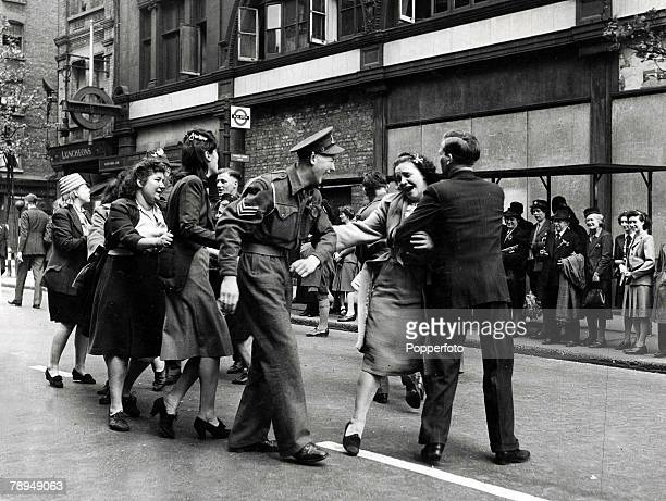 Volume 2 Page 128 Picture 6 World War Two London England 8th May Soldiers and civilians in ecstatic mood as they celebrate VE Day in the streets of...