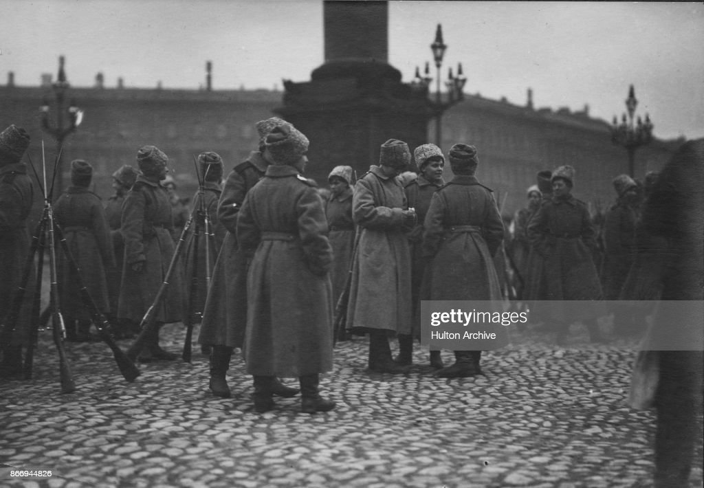 A group of soldiers from the Women's Battalion gathered in a square in Petrograd during the Russian Revolution, 1917. They are wearing overcoats and astrakhan hats. From The Russian Album.