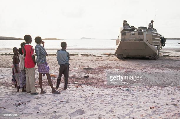 A group of Somali children watch as United States Marines drive a personnel carrier along the shoreline after making an amphibious landing on a...