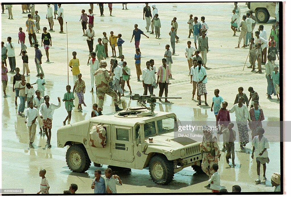 A group of Somalis gather around a US Marine humvee in an open space in Mogadishu
