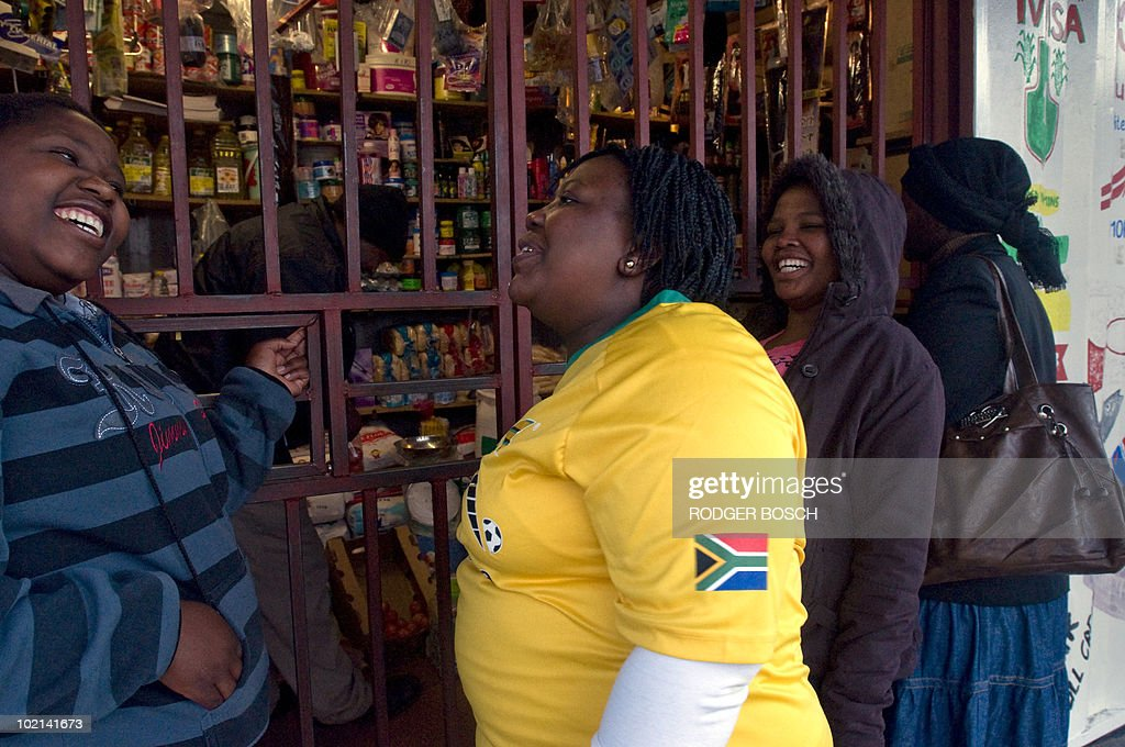 A group of South African supporters chat in front of a Spaza, or informal shop in an impoverished suburb about 20Km from the centre of Cape Town, on June 16, 2010 moments before South Africa take on Uruguay in their 2010 Football World Cup Group A match.