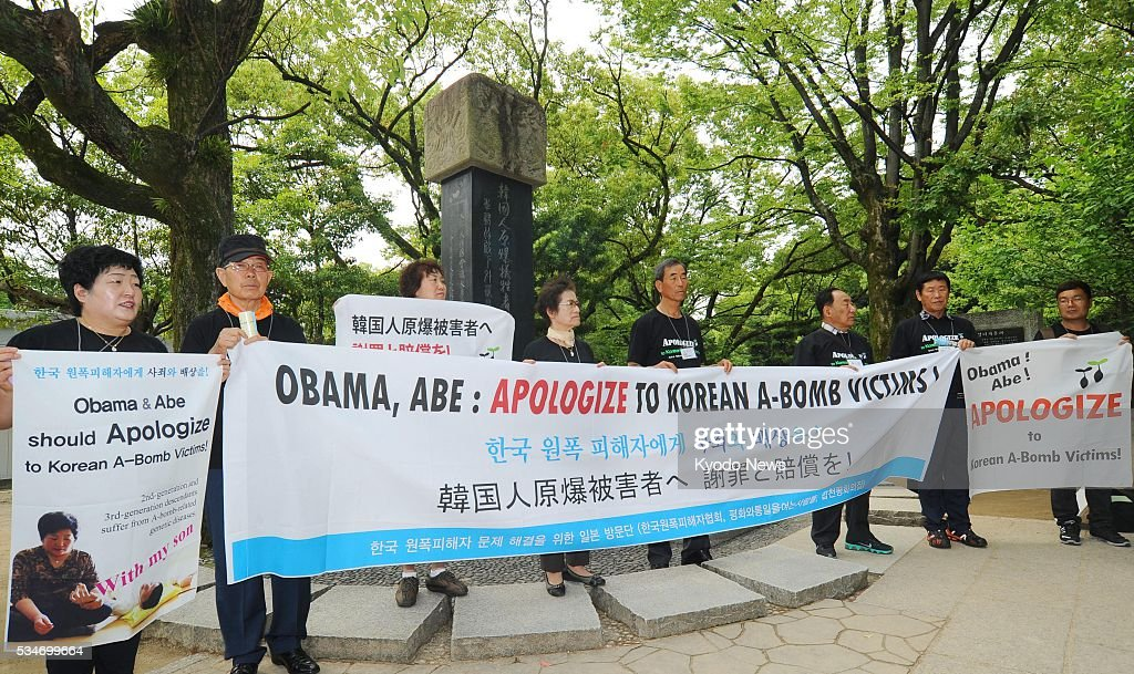 A group of South Korean survivors and descendants of survivors of the atomic bombing of Japan hold banners at the Peace Memorial Park in Hiroshima on May 27, 2016, calling on U.S. President Barack Obama to issue an apology and provide compensation for the suffering caused by the attacks. Obama will visit the atomic-bombed city later in the day.